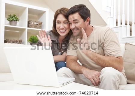 Happy man and woman couple in their thirties, sitting together at home on a sofa using a laptop computer to make a VOIP internet phone call and waving at the screen - stock photo
