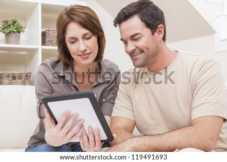 Happy man and woman couple in their thirties, sitting together at home on a sofa using a tablet computer - stock photo