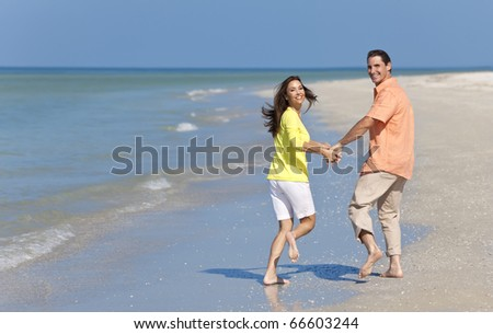Happy man and woman couple running, laughing and holding hands on a deserted beach with bright clear blue sky - stock photo