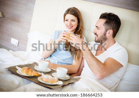 Happy man and woman having luxury hotel breakfast in bed together-stock - stock photo