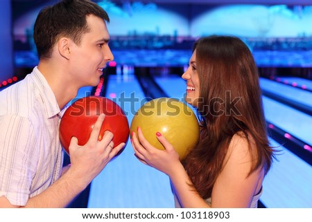 Happy man and woman hold balls and look at each other in bowling - stock photo