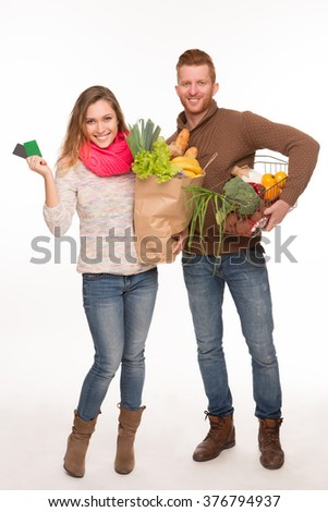 Happy man and woman holding grocery shopping bags isolated on white. Man and woman are going home from product shop. - stock photo