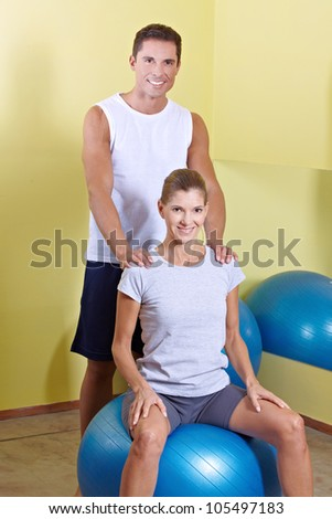 Happy man and woman in fitness center with gym ball - stock photo