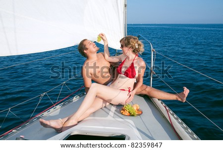 Happy man and woman on a  yacht - stock photo