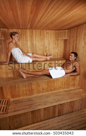 Happy man and woman sitting together in a wooden sauna - stock photo