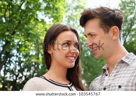 Happy man and woman stand in park and look at each other; green trees and sunny day; focus on girl - stock photo