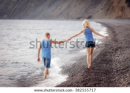 happy man and woman walking along the beach - stock photo