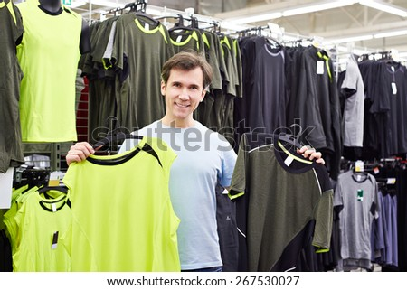 Happy man chooses for t-shirts in sport shop - stock photo