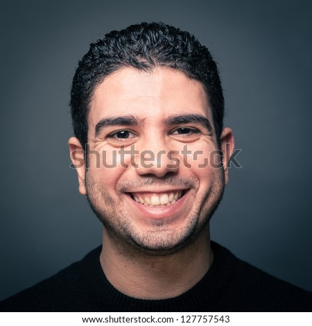 Happy man close up portrait against dark background. - stock photo