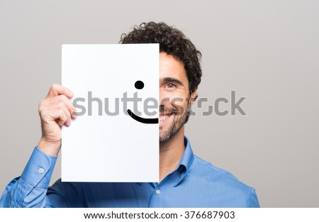 Happy man covering half his face with a smiling emoticon - stock photo