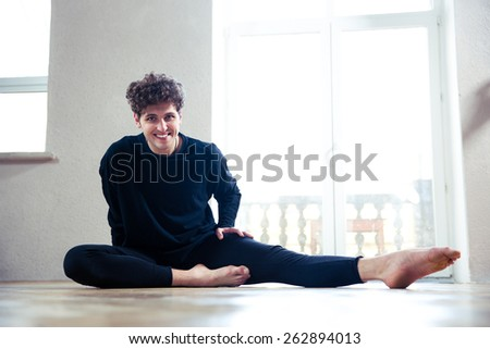 Happy man doing stretching exercise at gym - stock photo