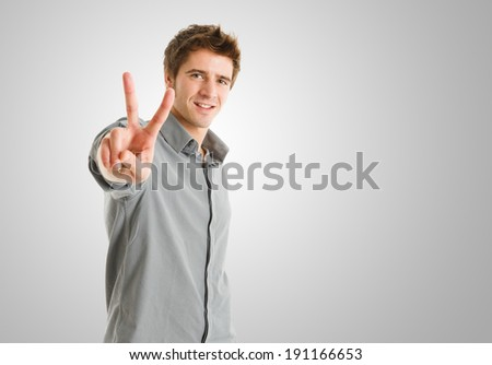 Happy man doing victory sign - stock photo