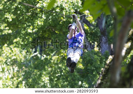 Happy Man Enjoying Zipline Adventure In The Forest - stock photo