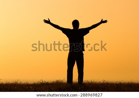 Happy man enjoys in sunset.Greeting the sunset - stock photo