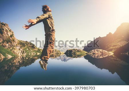 Happy Man Flying levitation jumping with lake and mountains on background Lifestyle Travel emotions concept outdoor  - stock photo