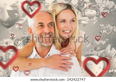 Happy man giving his partner a piggy back against grey valentines heart pattern - stock photo