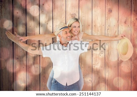 Happy man giving his partner a piggy back against light circles on black background - stock photo