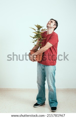 Happy man holding Cannabis plant and looking up. - stock photo