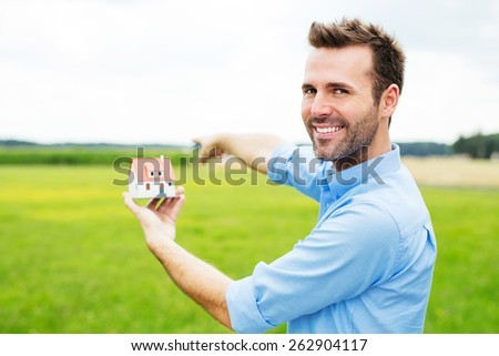 Happy man holding miniature showing place on field for new house - stock photo