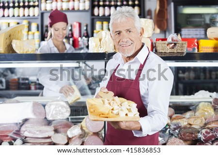 Happy Man Holding Various Cheese On Board In Store - stock photo