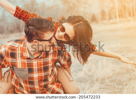 Happy man holds woman on his back, woman with flying gesture. Low contrast, with sunlight effect - stock photo