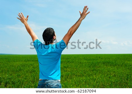happy man in blue t-shirt standing on green meadow - stock photo