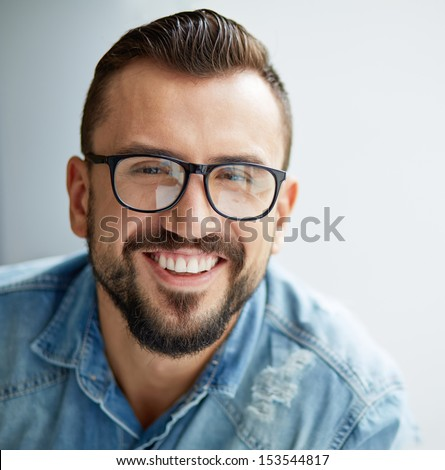 Happy man in denim shirt and eyeglasses looking at camera with toothy smile - stock photo