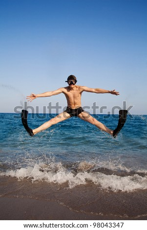 Happy man in goggles and flippers jumping at the beach - stock photo