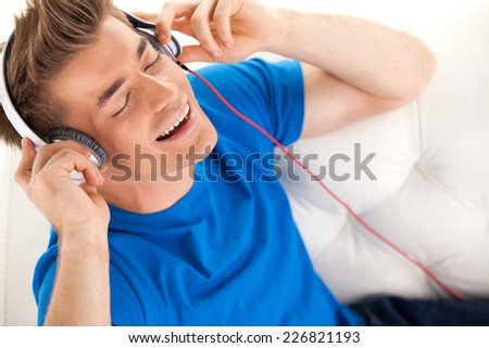 Happy man in headphones relaxing on sofa at home. handsome guy top view resting while singing song - stock photo