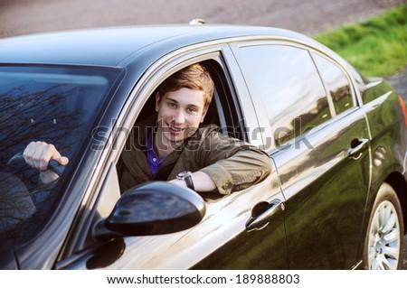 Happy man in his new car smiles - stock photo