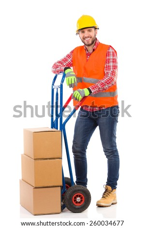 Happy man in yellow hardhat and orange reflective vest posing with a delivery cart and looking at camera. Full length studio shot isolated on white. - stock photo