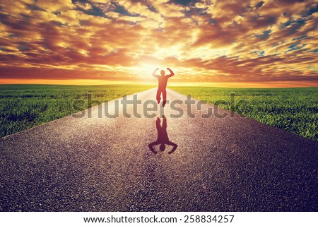 Happy man jumping on long straight road, way towards sunset sun. Travel, happiness, win, healthy lifestyle concepts. - stock photo