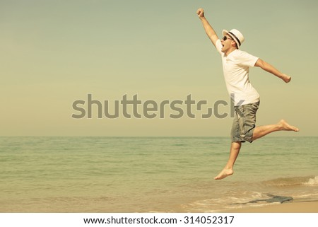Happy man jumping on the beach at the day time - stock photo