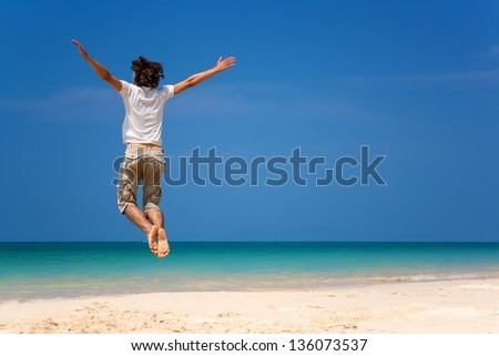 Happy man jumping on the beach in the sunny day - stock photo