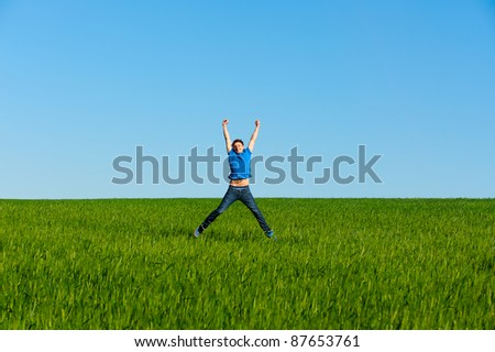 happy man jumping on the green field - stock photo