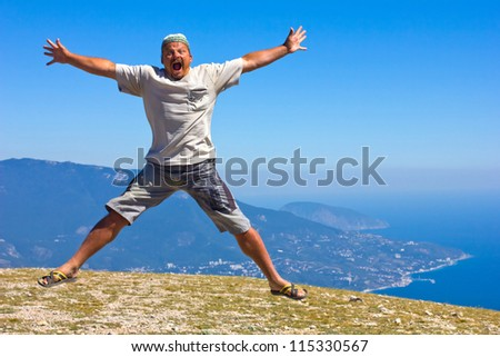 happy man jumping over the Crimean Mountains and the Black Sea - stock photo