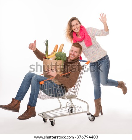 Happy man lying in shopping cart, holding bags with groceries and showing okey sign. Cheerful lady pushing shopping cart. - stock photo