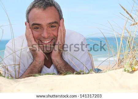 Happy man lying on the sand - stock photo