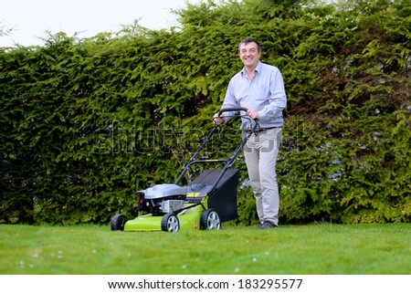 Happy man mowing the lawn in the backyard of his house at the free time on a sunny summer day - stock photo