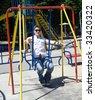 Happy man on child swing. - stock photo