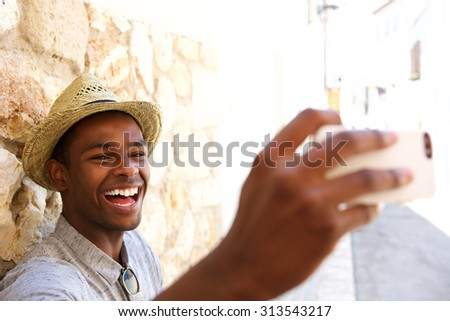 Happy man on vacation taking a selfie - stock photo