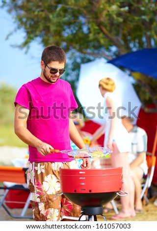 happy man prepares food on the grill, family picnic - stock photo