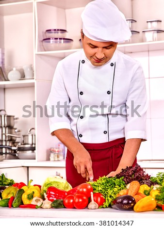 Happy man professional in chef hat cooking . - stock photo