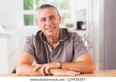 Happy man sitting at table in kitchen - stock photo