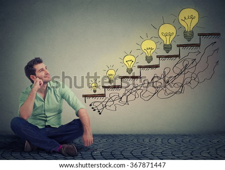 Happy man sitting on a floor in his office dreaming of business education success, promotion, company growth isolated gray wall texture background. Handsome guy looking up at growing up light bulbs  - stock photo