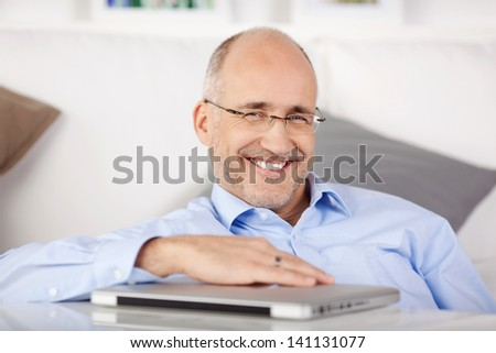 Happy man sitting on the floor and holding a laptop on table - stock photo