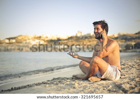 Happy man sitting on the sand doing a phone call - stock photo
