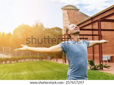 Happy man standing in a city garden with arms spread open. Selective focus - stock photo