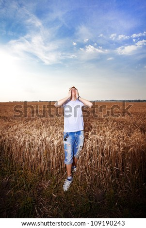 Happy man standing with closed arms on a wheat field - stock photo