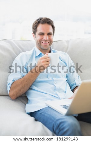Happy man using laptop sitting on sofa having a coffee at home in the living room - stock photo